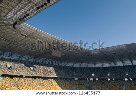 This is the modern stadium, seats are painted a yellow and a blue. The range of building colors blend well with blue sky. - stock photo