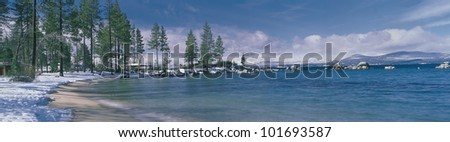 This is the sandy beach at Lake Tahoe. It shows the turquoise water in the winter after a snow storm. - stock photo