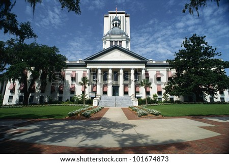 This is the State Capitol building in Florida. It has a large concrete stairway leading up to it with large columns holding up the facade. - stock photo