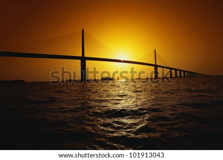 This is the Sunshine Bridge. It is one of the longest suspension bridges in North America. The ocean is shown in the foreground with the bridge in the distance. - stock photo