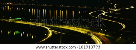 This is the Theodore Roosevelt Bridge over the Potomac River at night. There are streaked lights from the cars on the freeway and reflections from the lights on the road in the river. - stock photo