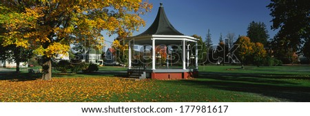 This is the town square. In the center is a gazebo. It is located on Main Street. There is autumn foliage in a park setting. We see Victorian style house with a gazebo has white columns and steps. - stock photo