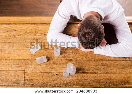 This is too much? Top view of drunk man in white shirt leaning at the bar counter while empty glasses standing near him  - stock photo