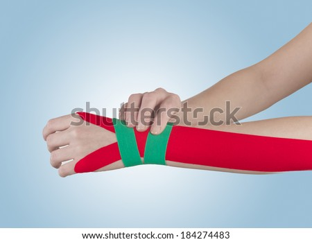 """This kind of taping is called """"Kinesiotape"""". Its purpose is to detonisize the muscle to reduce pain in wrist. - stock photo"""
