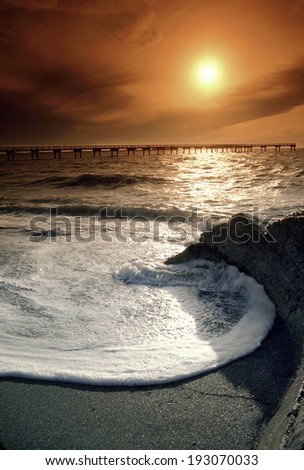 This large, circular wave wraps around the remains of an old lighthouse foundation creating a calm, peaceful sunset on the Florida Gulf Coast. - stock photo