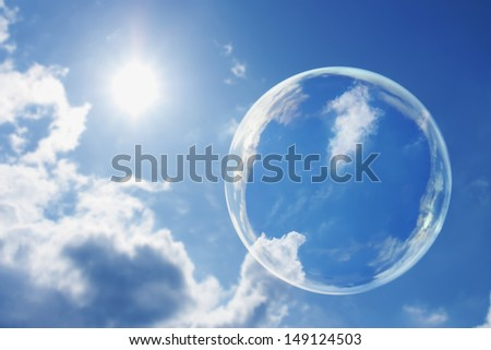 This large soap bubble floats calmly against a clear deep blue sky and clouds representing a natural 'Thought Bubble' on possible ideas for clean atmosphere, fresh air and a green environment. - stock photo