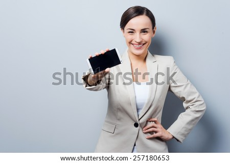 This mobile phone is for smart people. Beautiful young businesswoman stretching out mobile phone and looking at camera while standing against grey background - stock photo