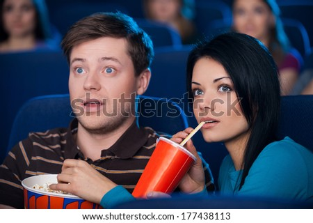 This movie is so exciting! Excited young couple eating popcorn and drinking soda while watching movie at the cinema  - stock photo