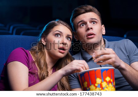 This movie is so scary! Shocked young couple eating popcorn and watching movie together while sitting at the cinema  - stock photo