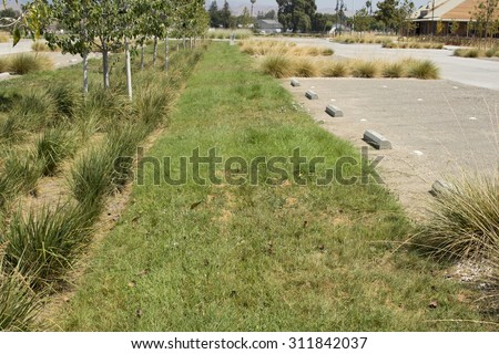 This new parking lot includes pervious pavement, landscaping, and bioswale areas to capture stormwater runoff. - stock photo