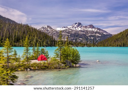 This red tent is a nice contrast with the turquoise water of Upper Joffre Lake in British Columbia, Canada - stock photo