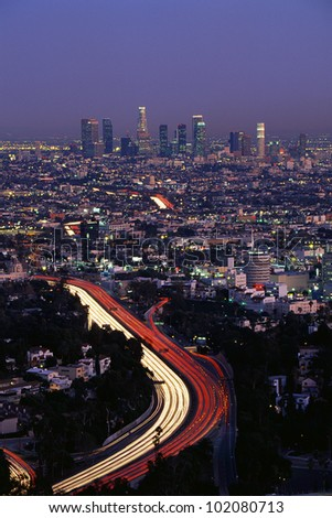 This shows the Hollywood Freeway and skyline at dusk. - stock photo