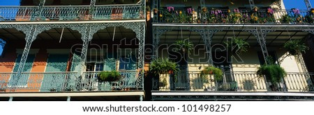 This shows two buildings in the historic French Quarter on Bourbon Street. The buildings have lattice work railings with potted flowers decorating the balconies. - stock photo