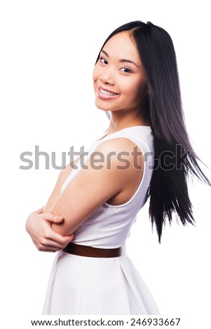 This smile is just for you! Beautiful young Asian woman in pretty dress keeping arms crossed and smiling while standing against white background   - stock photo