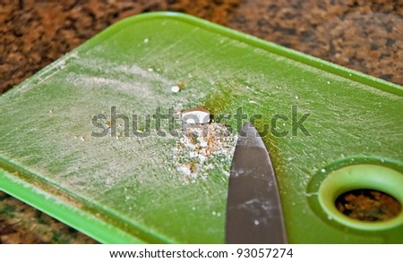 This stock image is a medical white pill, cut in half and crushed on a green cutting board with a knife. - stock photo
