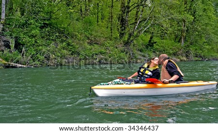 This sweet photo of romance shows a young Caucasian couple giving a kiss while on a mountain river kayaking. - stock photo