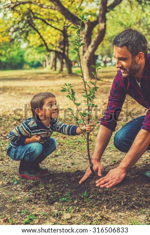 This tree will grow with you! Playful little boy helping his father to plant the tree while working together in the garden - stock photo