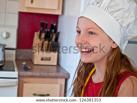 This 10 year old Caucasian girl is happy and smiling in the kitchen, while wearing a white chef's hat.  She's excited to be learning how to cook. - stock photo