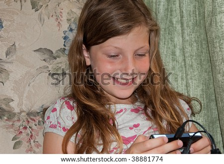 This young girl is happy and smiling while playing a video game. - stock photo