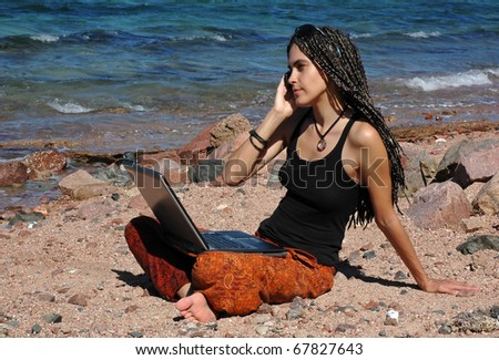 This young woman can be a professional freelancer or a student studying outdoors. She sits on a beach and uses her laptop and cellphone. - stock photo