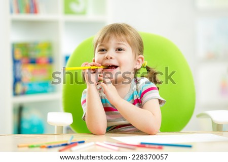 thoughful child girl drawing with colorful pencils - stock photo