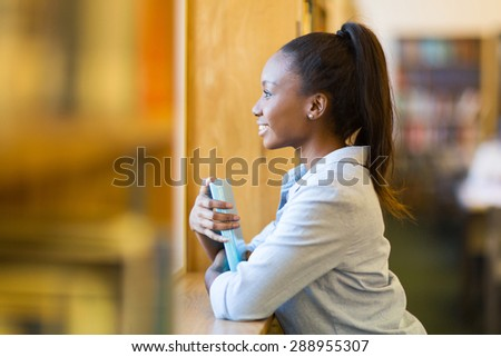 thoughtful african college girl in library - stock photo