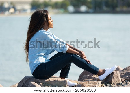thoughtful african woman sitting by the harbour - stock photo