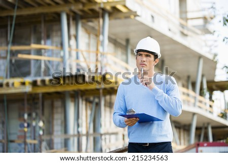 Thoughtful architect with clipboard and pen standing at site - stock photo