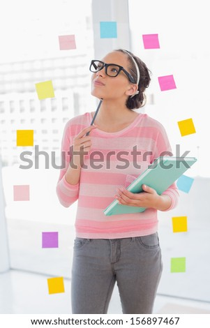 Thoughtful attractive artist holding her sketchpad while standing in her creative office - stock photo