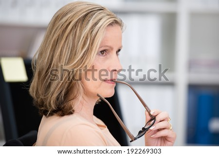 Thoughtful attractive middle-aged businesswoman standing holding the frame of her glasses to her mouth as she stares pensively into the distance - stock photo