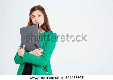 Thoughtful attractive young woman in green jacket holding folders and thinking over white background - stock photo