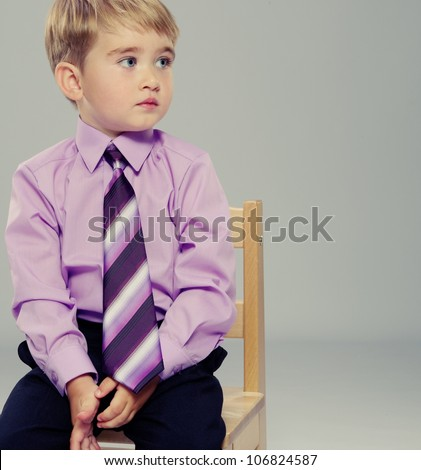 Thoughtful baby boy sitting on a chair - stock photo