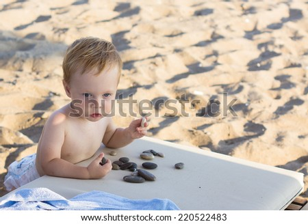 thoughtful baby boy sitting on the beach - stock photo