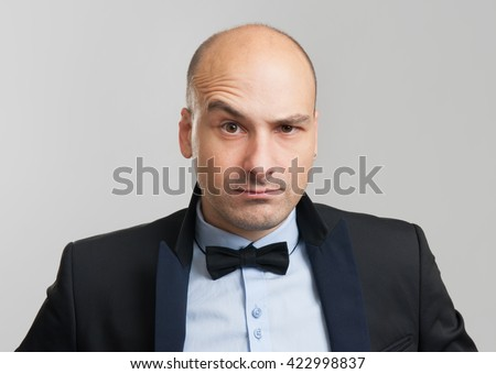 thoughtful bald business man with a raised eyebrow - stock photo