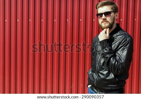 Thoughtful bearded young guy. Wearing a stylish clothes and sunglasses. On the street, on red corrugated fence background - stock photo