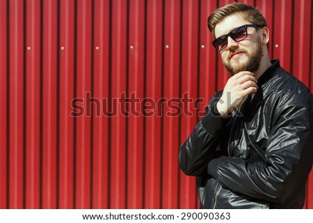 Thoughtful bearded young man. Wearing a modern clothes and sunglasses. On the street, on red corrugated fence background - stock photo
