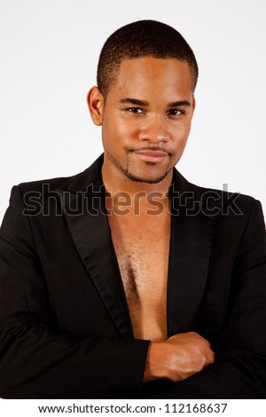 Thoughtful black man with no shirt on, in a black tux jacket - stock photo