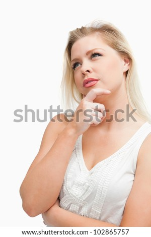 Thoughtful blonde woman looking up while standing against a white background - stock photo