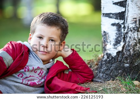 Thoughtful boy in red jacket lying next to tree, copyspace, looking at camera - stock photo