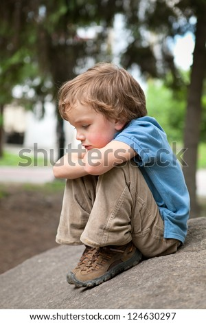 Thoughtful boy sitting on rock in park - stock photo