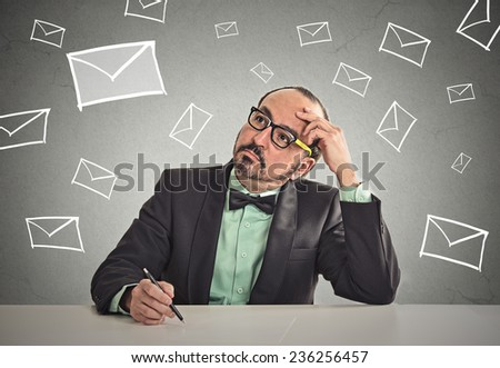 Thoughtful business man sitting at table waiting for life changing email job interview letter isolated office grey wall background copy space. Human face expression emotion feeling body language - stock photo