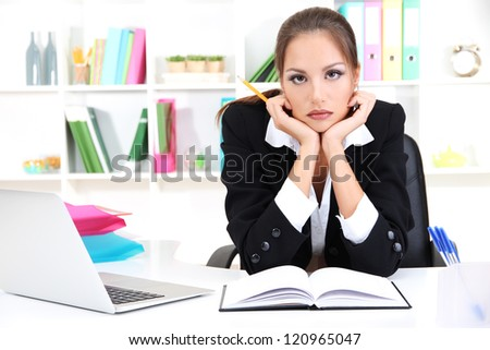 Thoughtful business woman with documents and notebook in office - stock photo