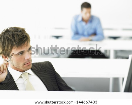 Thoughtful businessman at computer desk with male colleague in background - stock photo