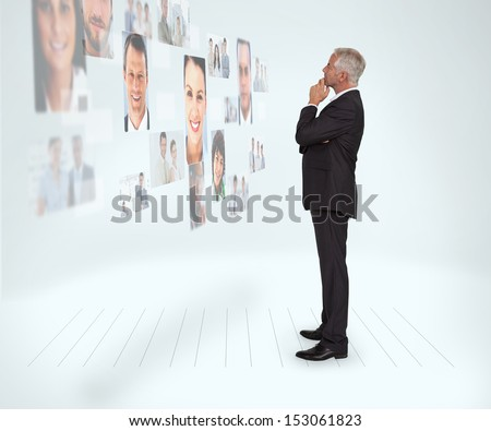 Thoughtful businessman looking at a wall covered by profile pictures on white background - stock photo