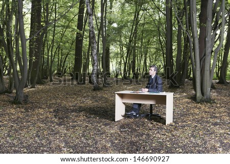 Thoughtful businessman looking away while sitting at desk in middle of forest - stock photo