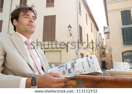 Thoughtful businessman reading the classified section of a newspaper while having a coffee outdoors. - stock photo