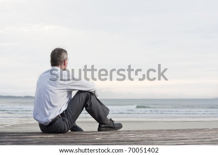Thoughtful businessman sitting on a beach and looking at the sea - stock photo