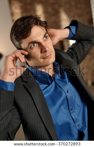 Thoughtful businessman talking on mobilephone, looking up, hand behind ear. - stock photo