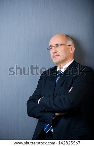 Thoughtful businessman with arms crossed looking away while standing against blue wall - stock photo