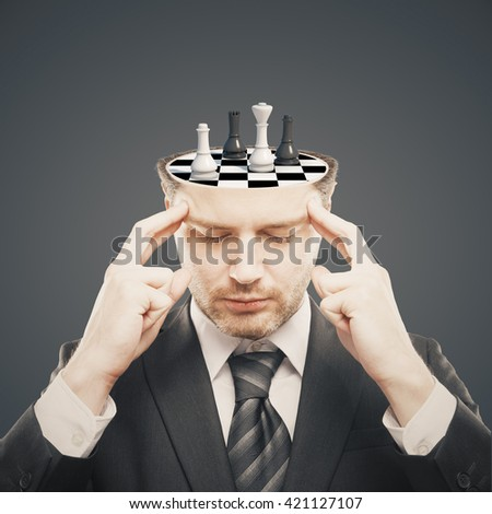 Thoughtful businessman with chess board instead of brain on grey background. Brainstorming concept - stock photo